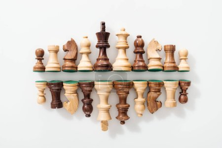 top view of rows made of wooden chess figures on white background