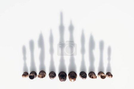 Photo pour Vue du haut des figures d'échecs en rangée avec des ombres sur fond blanc - image libre de droit