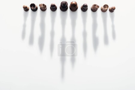 Photo for Top view of brown chess figures with long shadows on white background - Royalty Free Image