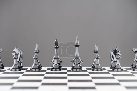black and white chessboard with black chess figures isolated on grey