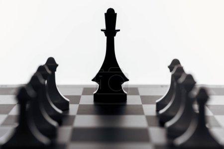 Photo pour Mise au point sélective de l'échiquier de la reine noire et pions isolées sur blanc - image libre de droit