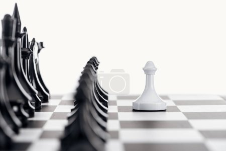 Photo for Selective focus of chessboard with black chess figures and white pawn in front isolated on white - Royalty Free Image