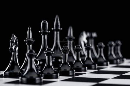 selective focus of chessboard with black chess figures isolated on black