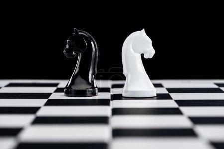 селективный фокус шахматной доски и белых и черных рыцарей, изолированных на черном