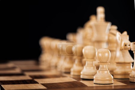 selective focus of beige and brown wooden chessboard with chess figures isolated on black