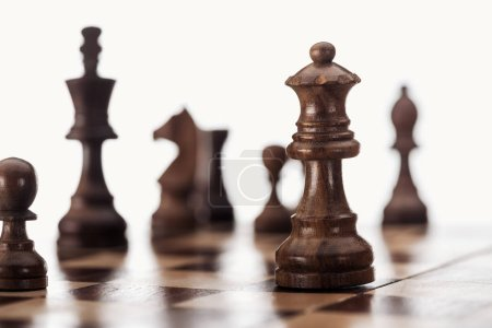 Photo for Selective focus of wooden chessboard with dark brown chess figures isolated on white - Royalty Free Image