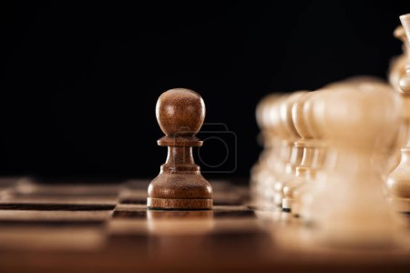 selective focus of wooden chessboard with chess pieces and pawn in front isolated on black
