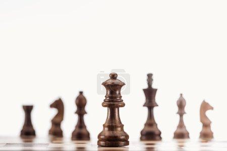 Photo pour Mise au point sélective de la reine en bois brune sur échiquier isolé sur blanc - image libre de droit