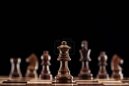 Photo pour Mise au point sélective de la reine en bois brune sur échiquier isolée sur fond noir - image libre de droit