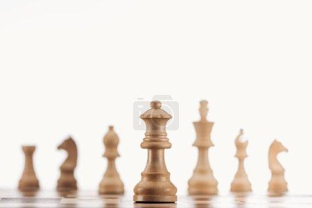Photo pour Mise au point sélective de la reine en bois beige sur échiquier isolé sur blanc - image libre de droit