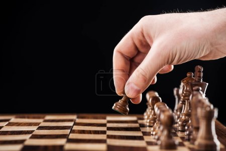 Photo for Partial view of man doing move on wooden chessboard isolated on black - Royalty Free Image