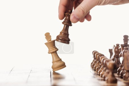 Photo for Partial view of man holding queen near king on wooden chessboard isolated on white - Royalty Free Image
