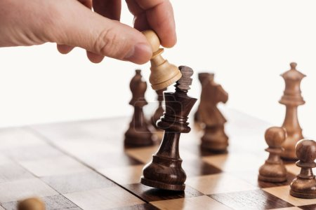partial view of man holding pawn above wooden chessboard isolated on white
