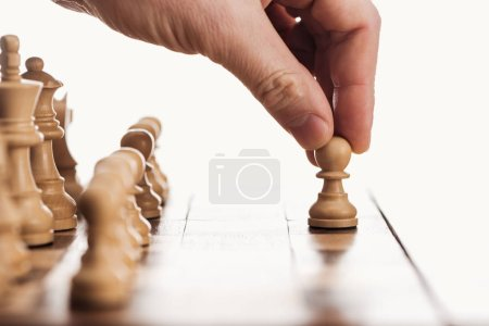 Photo for Partial view of man doing move with pawn on wooden chessboard isolated on white - Royalty Free Image