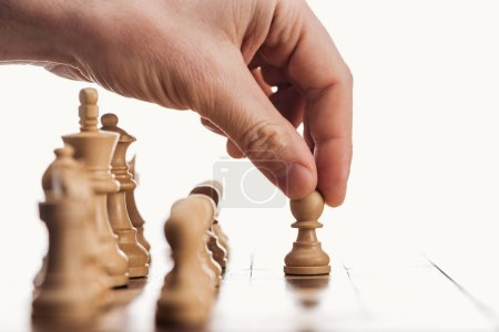 cropped view of man doing move with beige pawn on wooden chessboard isolated on white