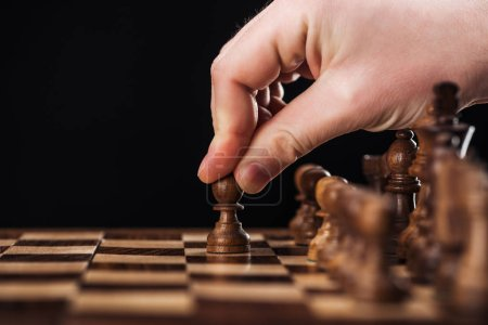 cropped view of man doing move with pawn on wooden chessboard isolated on black