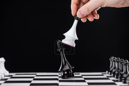 Photo for Cropped view of man doing move with queen on chessboard isolated on black - Royalty Free Image