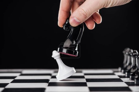 Photo for Partial view of man doing move with knight on chessboard isolated on black - Royalty Free Image