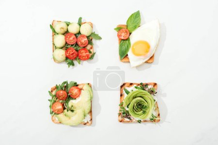 Photo for Top view of toasts with cut vegetables and prosciutto on white surface - Royalty Free Image