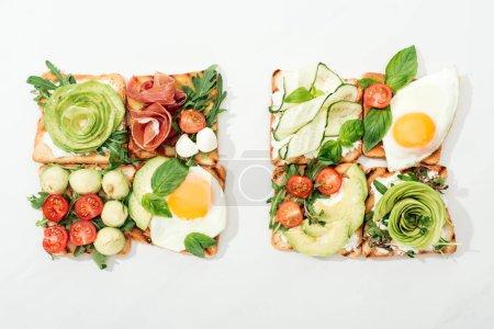 Foto de Vista superior de tostadas con jamón serrano y verduras cortadas en la superficie blanca - Imagen libre de derechos