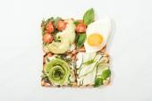 """Постер, картина, фотообои """"Вид сверху тосты с жареным яйцом и нарезанные овощи на белой поверхности"""""""