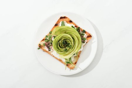 Photo for Top view of toast with sliced avocado and garden cress on plate on white surface - Royalty Free Image