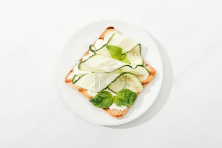 Photo for Top view of toast with sliced cucumber and basil on plate on white surface - Royalty Free Image