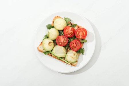 Photo for Top view of toast with cherry tomatoes and arugula on plate on white surface - Royalty Free Image