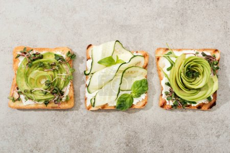Photo for Top view of toasts with cut vegetables on texture surface - Royalty Free Image