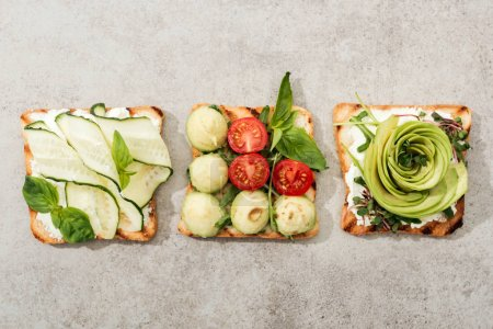 Photo for Top view of toasts with cut vegetables on textured surface - Royalty Free Image