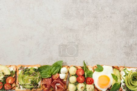 Photo for Top view of toasts with cut vegetables and prosciutto on textured surface - Royalty Free Image