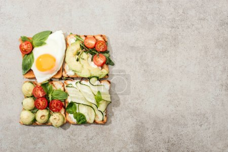 Photo for Top view of toasts with cut vegetables and fried egg on textured surface - Royalty Free Image