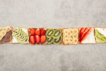 Photo for Top view of toasts with cut fruits, berries and peanuts on textured surface - Royalty Free Image