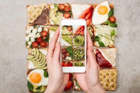 Photo for Partial view of woman holding smartphone and taking photo of toasts with fruits and vegetables - Royalty Free Image