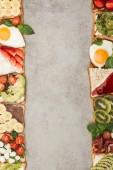 """Постер, картина, фотообои """"Вид тосты с жареным яйцом сверху, вырезать овощи и фрукты на текстурированной поверхности"""""""