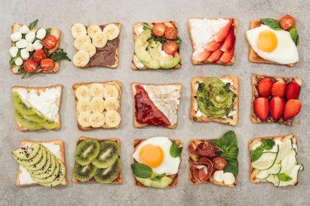 Photo pour Vue de dessus des toasts aux œufs frits, légumes coupés et fruits sur surface texturée - image libre de droit