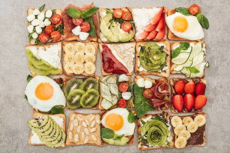 Photo for Top view of toasts with fried eggs, cut vegetables and fruits on textured surface - Royalty Free Image
