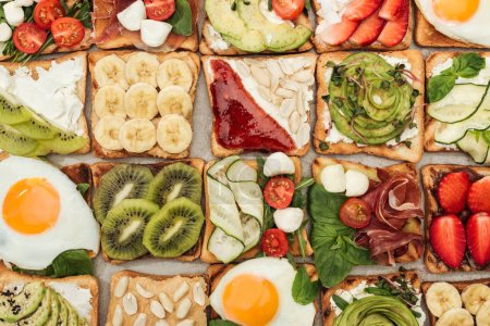 Photo for Top view of toasts with fried eggs, peanuts, cut vegetables and fruits - Royalty Free Image