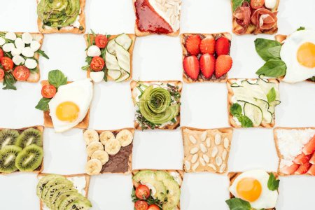 Photo for Top view of toasts with cut fruits, vegetables and peanuts on white surface - Royalty Free Image