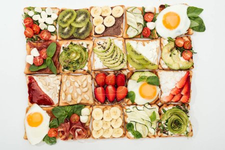 Photo for Top view of toasts with cut fruits, vegetables and peanuts on white - Royalty Free Image