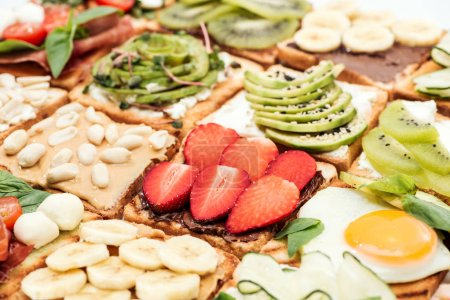 Photo for Toasts with cut fruits, strawberry. fried egg and peanuts - Royalty Free Image