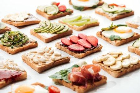 Toasts mit geschnittenen Früchten, gebratenen Eiern und Erdnüssen auf weiß