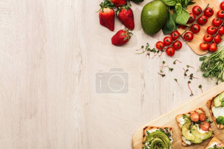 Photo for Top view of toasts with vegetables and ingredients on wooden table with copy space - Royalty Free Image