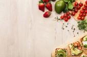 """Постер, картина, фотообои """"вид сверху тосты с овощами и ингредиенты на деревянный стол с копией пространства"""""""