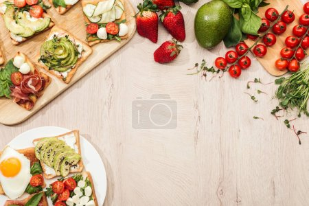 top view of toasts with vegetables and prosciutto, greenery and ingredients on wooden table with copy space