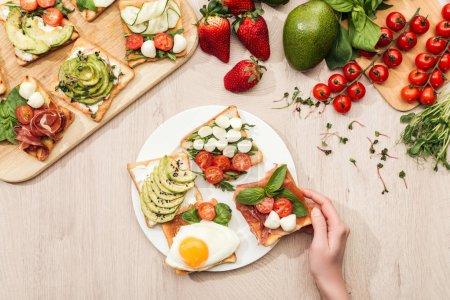 Foto de Vista superior de la mujer con deliciosas tostadas verduras e ingredientes en la mesa de madera - Imagen libre de derechos