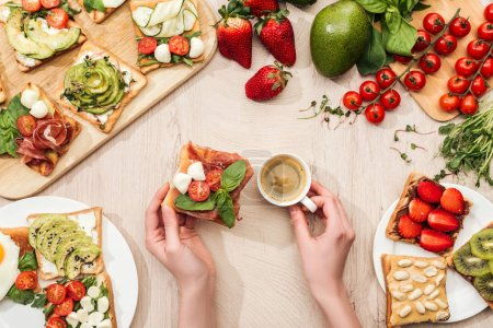 Photo for Top view of woman holding cup of coffee at table with ingredients, greenery and toasts with vegetables and prosciutto - Royalty Free Image