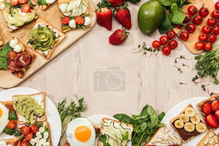 Photo for Top view of toasts with vegetables, fruits and prosciutto with greenery and ingredients on wooden table - Royalty Free Image