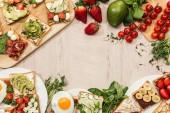 """Постер, картина, фотообои """"вид сверху тосты с овощами, фруктами и прошутто с зеленью и ингредиенты на деревянный стол"""""""