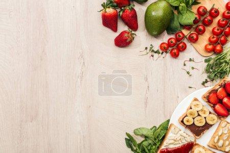 Photo pour Vue de dessus des toasts avec des fruits sur la plaque et les ingrédients sur la table en bois avec espace copie - image libre de droit